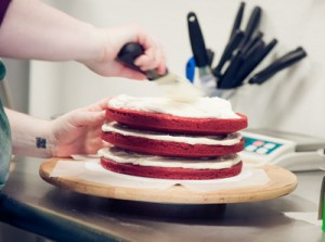 Chef Sara Fatell of Grassroots Gourmet frosts a red velvet cake.